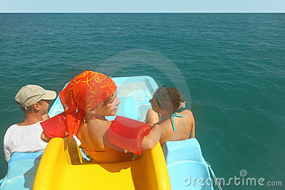 Family on pedal boat with slide in sea