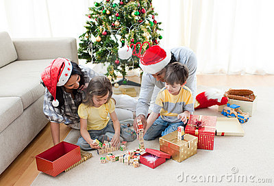 Family playing with Christmas presents at home