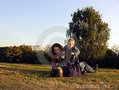Family plays autumn on sundown on glade