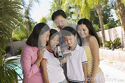 Family by pool in backyard Looking at Video Camera Screen front view