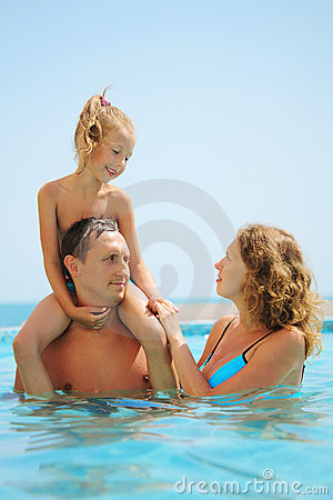 Family in pool. Daughter sits on fathers shoulder