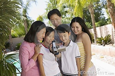 Family by pool Looking at Video Camera Screen