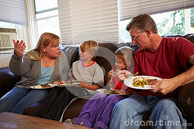 Family With Poor Diet Sit On Sofa Eating Meal And Arguing