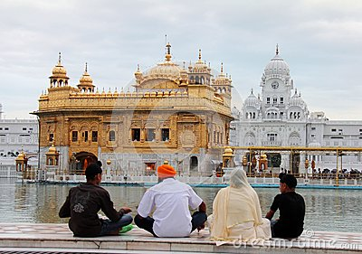 A family praying in front of golden temple Editorial Stock Image