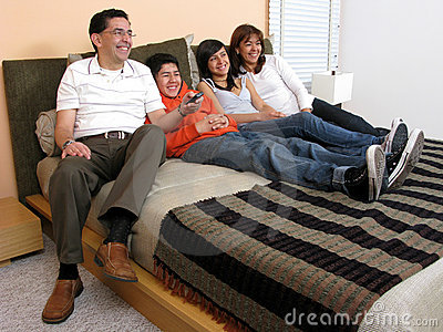 Family reclining in bed