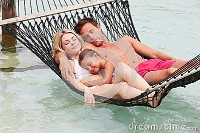 Family Relaxing In Beach Hammock