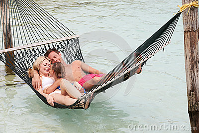 Family Relaxing In Beach Hammock