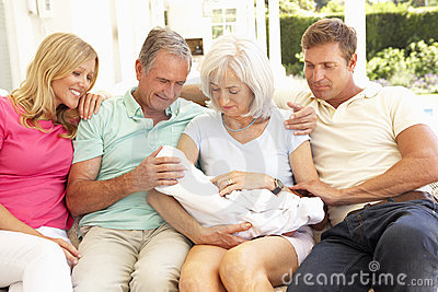Family Relaxing Together On Sofa With Newborn Baby
