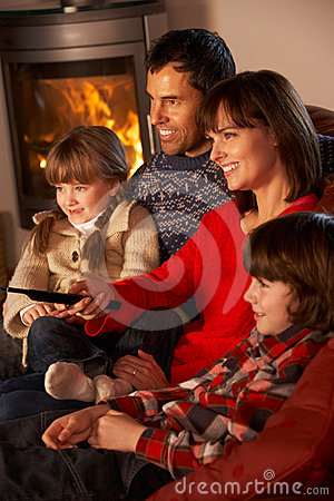 Family Relaxing Watching TV By Cosy Log Fire