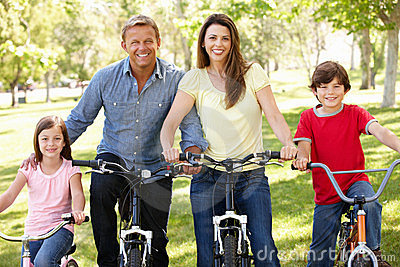 Family riding bikes in park