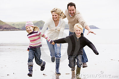 Family running on beach holding hands