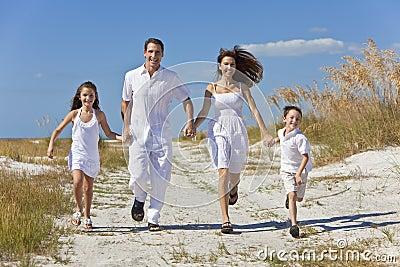 Family Running Having Fun At Beach