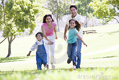 Family running outdoors holding hands and smiling