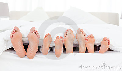 Family s feet in the bed