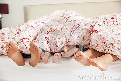 Family s Feet Poking Out From Duvet In Bed