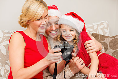 Family in santa helper hats looking at pictires