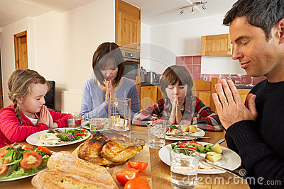 Family Saying Grace Before Eating Lunch