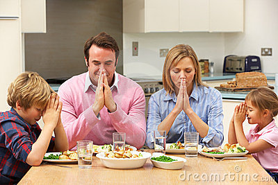 Family saying grace before meal