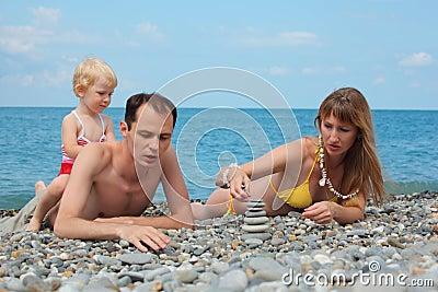 Family on sea coast build pyramid