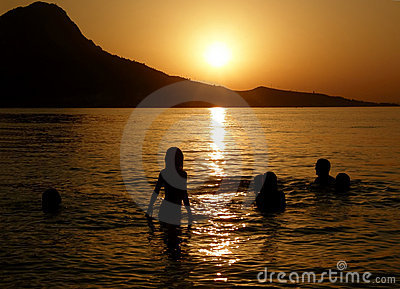 Family in sea at sunset