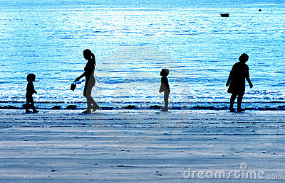 Family silhouetted on a blue evening beach