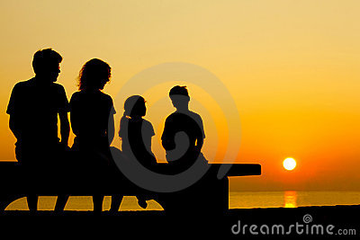 Family sit on bench on beach