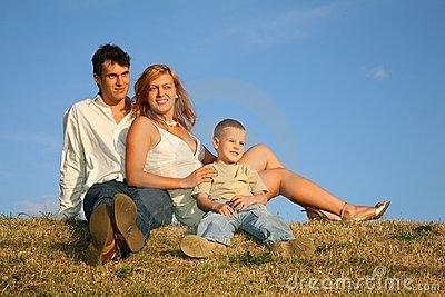 Family sit on the meadow