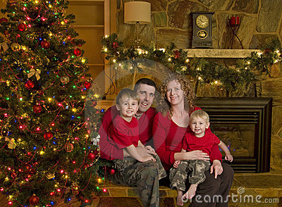 Family Sits beside Christmas Tree