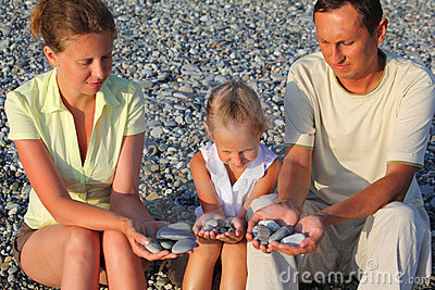 Family sits in pebbly beach and holding pebbles