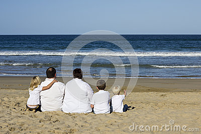 Family sitting on beach watching ocean