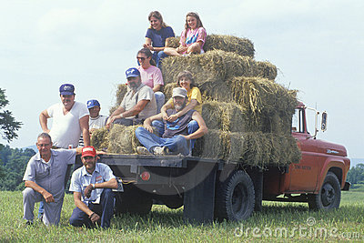 Family sitting with hay bales on truck Editorial Image