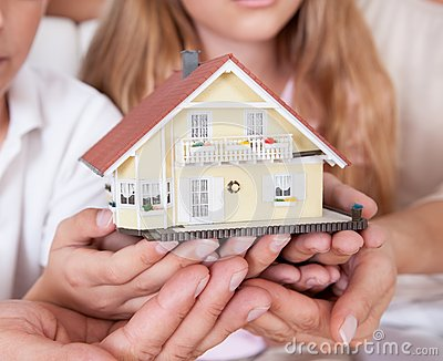 Family Sitting Holding Miniature Model Of House