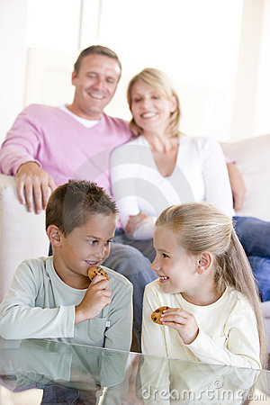 Family sitting in living room eating cookies