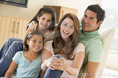 Family sitting in living room smiling