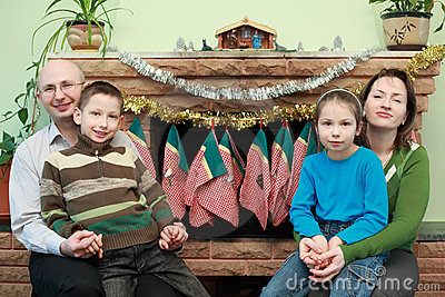 Family sitting near fireplace, Christmas ornaments