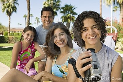 Family sitting outdoors taking video
