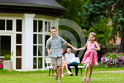 Family sitting and playing in front of their home
