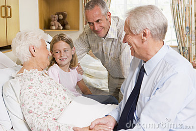 Family Sitting With Senior Woman In Hospital