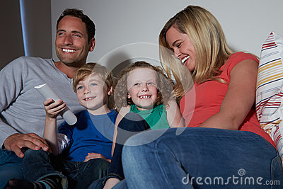 Family Sitting On Sofa Watching TV Together