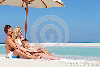 Family Sitting Under Umbrella On Beach Holiday
