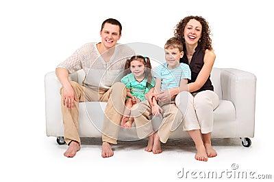 Family sitting on white leather sofa