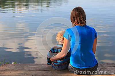 family sitting on wooden dock