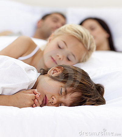 Family sleepimg in parent s bed