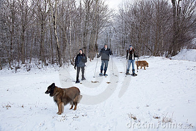 Family snowshoeing with dogs