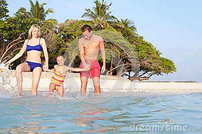 Family Splashing In The Sea On Tropical Beach Holiday