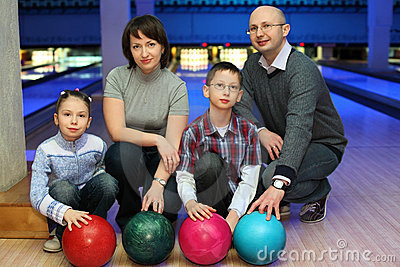 Family of squatting in club for bowling
