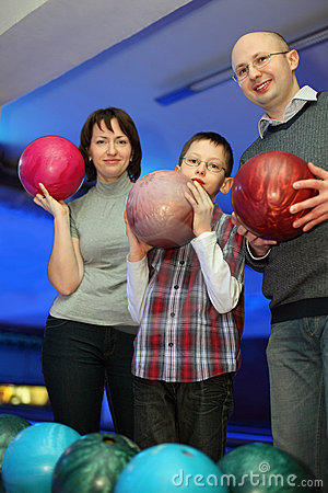Family stand alongside and hold balls for bowling