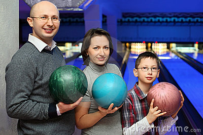 Family stand and hold balls for bowling