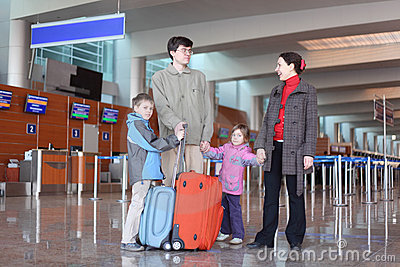 Family standing in airport hall with suitcases