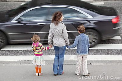 Family standing near cross road, behind